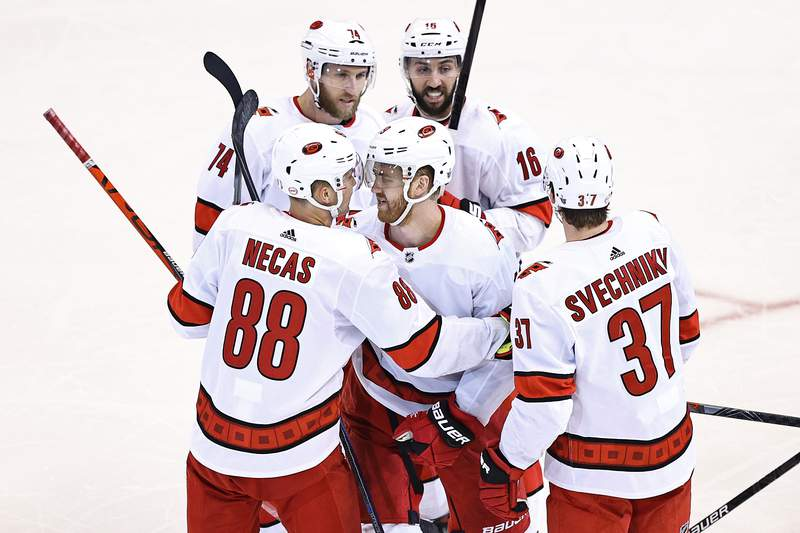 Dougie Hamilton of the Carolina Hurricanes is congratulated by his teammates after scoring a goal against the Boston Bruins during the third period in Game Two of the Eastern Conference First Round during the 2020 NHL Stanley Cup Playoffs at Scotiabank Arena on August 13, 2020 in Toronto, Ontario.