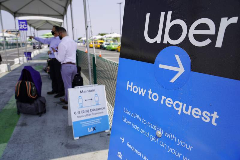 FILE - In this Aug. 20, 2020, file photo travellers request an Uber ride at Los Angeles International Airport, USA. The San Francisco-based ride hailing giant Uber said Thursday April 29, 2021, it aims to recruit 20,000 more drivers in the U.K. to help fill swelling demand for rides as the country's coronavirus lockdown restrictions ease. (AP Photo/Damian Dovarganes, File)