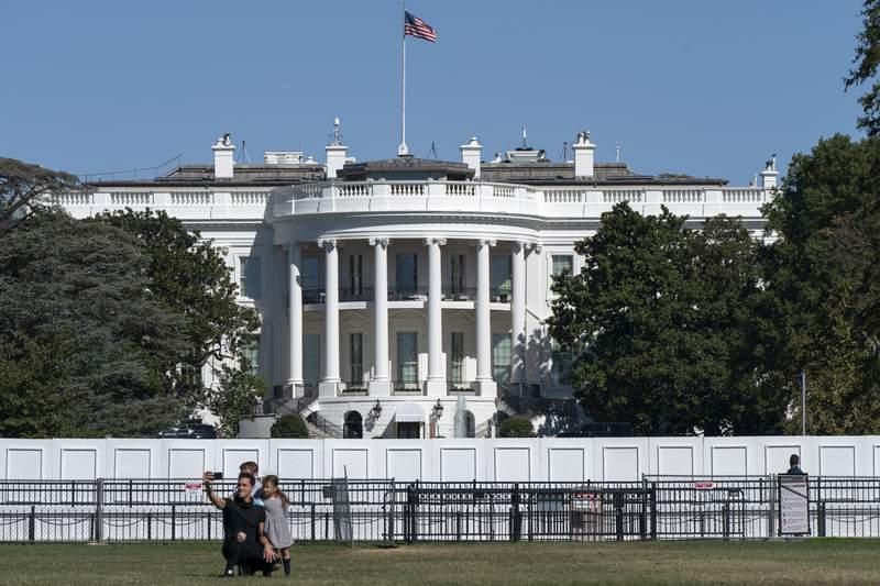 A family takes group portrait, Thursday, Oct. 8, 2020, outside of the White House in Washington. (AP Photo/Jacquelyn Martin)