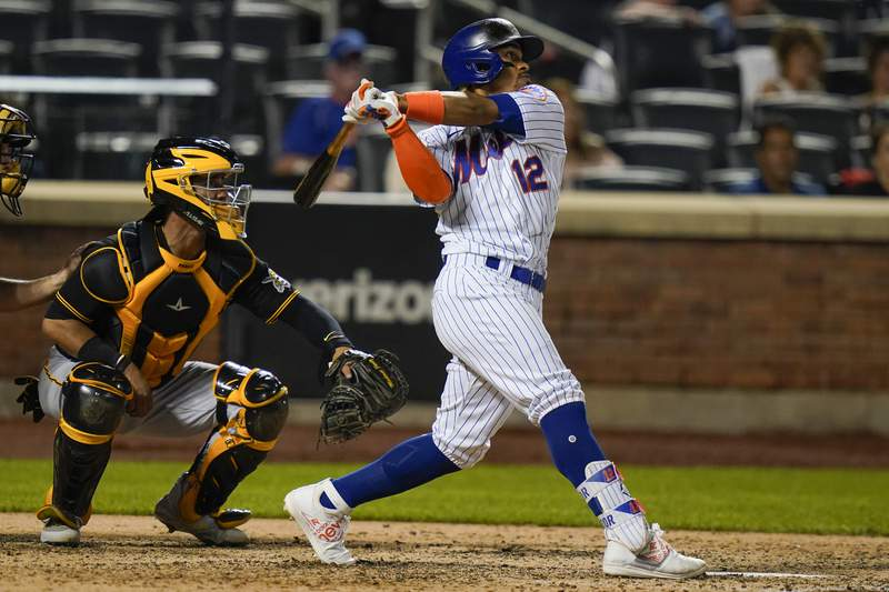 Pittsburgh Pirates catcher Michael Perez watches as New York Mets' Francisco Lindor, right, follows through on a grand slam home run during the sixth inningof a baseball game Friday, July 9, 2021, in New York. (AP Photo/Frank Franklin II)