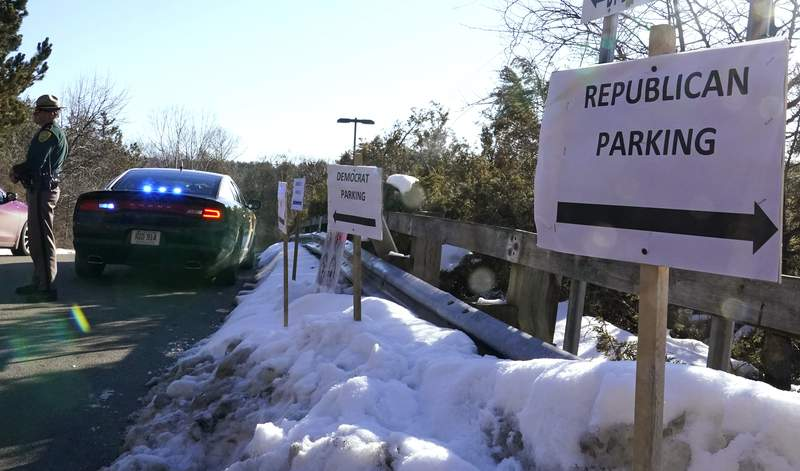 FILE - In this Feb. 24, 2021, file photo, a sign directs Republican and Democrat legislators to their parking areas as a N.H. State Trooper watches the flow of traffic prior to a New Hampshire House of Representatives session held at NH Sportsplex, due to the coronavirus in Bedford, N.H. Amid calls to dial back hyper political partisanship, two letters are among the obstacles standing in the way. Republicans, including the lawyers who defended former President Donald Trump during last weeks impeachment trial, routinely drop the i-c when referring to the Democratic Party or its policies. (AP Photo/Charles Krupa, File)