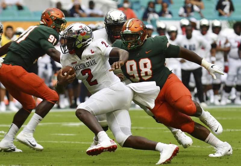 Jackson State quarterback Shedeur Sanders looks for running room as Florida A&M defensive lineman Stanley Mentor follows on the play in the first quarter of an NCAA college football game, Sunday, Sept. 5, 2021, in Miami Gardens, Fla.