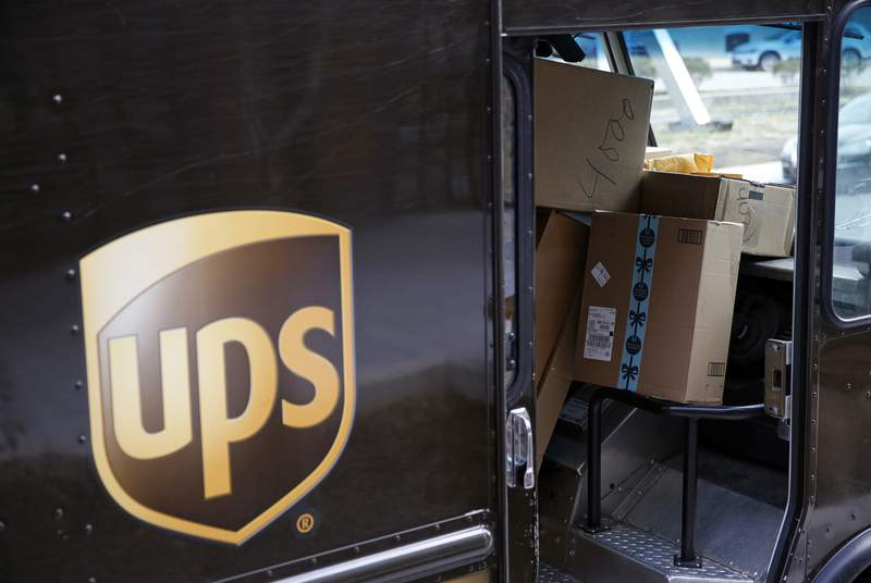 FILE - In this Dec. 19, 2018, file photo packages await delivery inside of a UPS truck in Baltimore. United Parcel Service Inc. reported a 13% drop in first-quarter profit, to $965 million, as stay-at-home orders generated deliveries to peoples homes but not enough to offset the higher costs and a drop in business deliveries. UPS said Tuesday, April 28, 2020 that the coronavirus outbreak has created significant headwinds. (AP Photo/Patrick Semansky, FIle)