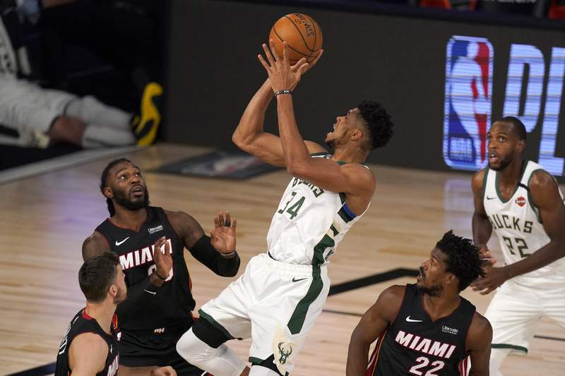 FILE - Miami Heat's Goran Dragic, bottom left, Jae Crowder, top left, and Jimmy Butler (22) defend as Milwaukee Bucks' Giannis Antetokounmpo (34) shoots during the first half of an NBA basketball conference semifinal playoff game inin Lake Buena Vista, Fla., in this Monday, Aug. 31, 2020, file photo. Bucks Khris Middleton, right rear, looks on. Having the NBAs best regular-season record and the leagues MVP each of the last two years hasnt paid off for the Bucks in the playoffs. Theyre hoping an offseason overhaul of their roster will help them earn the title that has eluded this franchise since 1971 and make sure two-time reigning MVP Giannis Antetokounmpo stays in Milwaukee for years to come.(AP Photo/Mark J. Terrill, File)