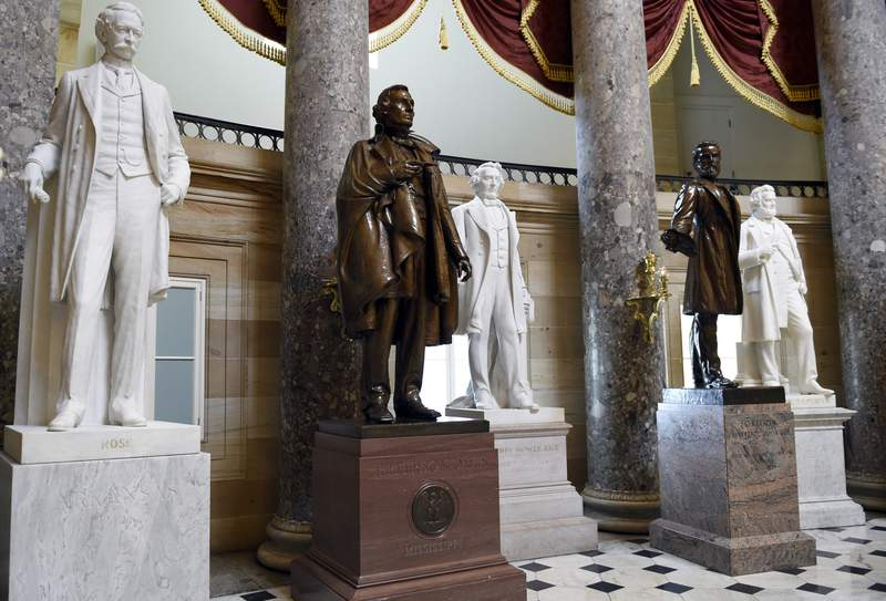 FILE - In this June 24, 2015 file photo, a statue of Jefferson Davis, second from left, president of the Confederate States from 1861 to 1865, is on display in Statuary Hall on Capitol Hill in Washington. House Speaker Nancy Pelosi is demanding that statues of Confederate figures such as Jefferson Davis be removed from the U.S. Capitol. (AP Photo/Susan Walsh, File)