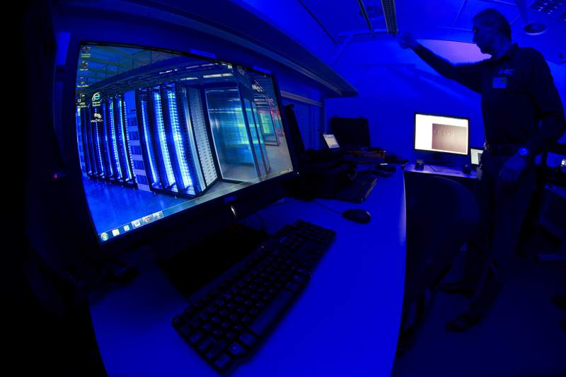 """FILE - This Friday Jan. 11, 2013 file photo of a member of the Cybercrime Center as he turns on the light in a lab during a media tour at the occasion of the official opening of the Cybercrime Center at Europol headquarters in The Hague, Netherlands. Dutch and French police have broken into an encrypted communications network used by organized crime gangs, allowing them to """"look over the shoulders"""" of criminals in real time as they planned drug trafficking, arms sales, assassinations and torture, officers announced Thursday. (AP Photo/Peter Dejong, File)"""