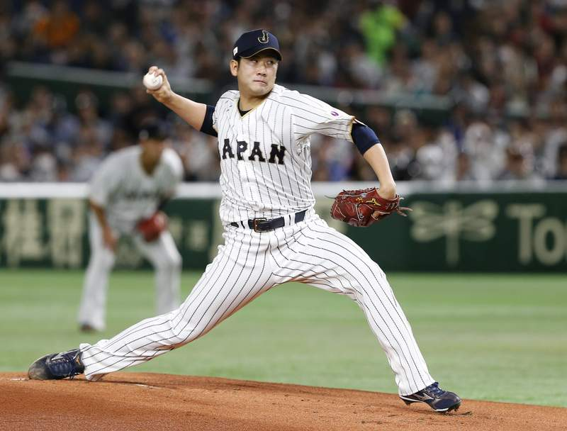 FILE - In this March 14, 2017, file photo, Japan starting pitcher Tomoyuki Sugano throws to a Cuba batter during the first inning of a second-round game at the World Baseball Classic in Tokyo. Japanese star pitcher Tomoyuki Sugano has been posted by the Yomiuri Giants and is available for bidding to major league teams. The bidding starts at 8 a.m. EST Tuesday, Dec. 8, 2020 and runs through 5 p.m. EST on Jan. 7. (AP Photo/Toru Takahashi, File)