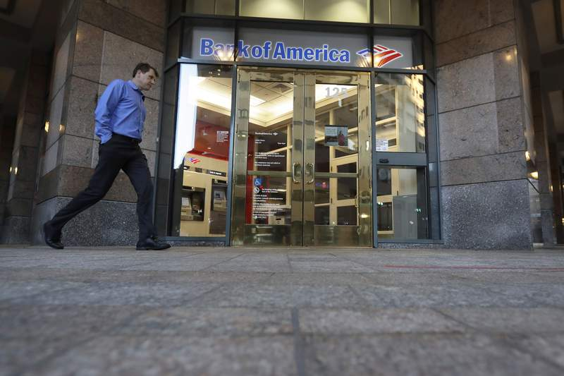 FILE - In this Oct. 14, 2019 file photo a passer-by walks past the entrance to a Bank of America ATM, in Boston.  Bank of America Corp. says profit fell 15.6% to $4.88 billion in the third quarter from $5.78 billion a year ago. The bank, based in Charlotte, North Carolina, said Wednesday, Oct. 14, 2020, that it had earnings of 51 cents per share.  (AP Photo/Steven Senne, File)