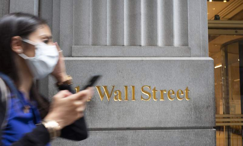 FILE - In this June 30, 2020 file photo, a woman wearing a mask passes a sign for Wall Street during the coronavirus pandemic. Stocks are starting another week with modest gains on Wall Street, and the S&P 500 is making its latest run at its record high.  (AP Photo/Mark Lennihan, File)