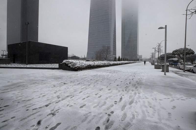 Un hombre trota en el distrito comercial de Madrid, viernes 8 de enero de 2021. Espaa est en alerta debido a un frente fro que ha cubierto de nieve buena parte del pas y trastornado el transporte. Las autoridades dicen que el clima puede empeorar durante el fin de semana. (AP Foto/Paul White)