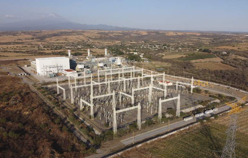 FILE - In this Feb. 22, 2020 file photo, a newly built power generation plant that is part of a mega-energy project including a natural gas pipeline traversing three states is seen with the Popocatepetl Volcano in the background near Huexca, Morelos state, Mexico. Mexico vowed on Feb. 4, 2021, to continue with attempts to limit private power generation after the Supreme Court ruled against President Andrs Manuel Lpez Obradors attempt to block permits for renewable power plants and give priority to older, more polluting, state-owned power plants. (AP Photo/Eduardo Verdugo, File)