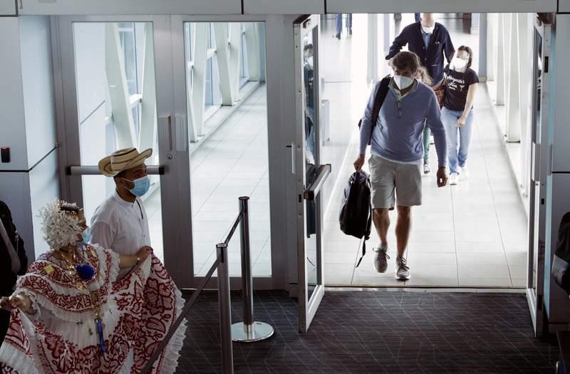 Los pasajeros son recibidos por artistas con vestimentas tradicionales cuando llegan al Aeropuerto Internacional de Tocumen en la Ciudad de Panam, el lunes 12 de octubre de 2020. Panam levant el lunes un amplio espectro de restricciones relacionadas con la pandemia de COVID-19, incluida la reapertura de vuelos internacionales, hoteles, casinos y actividades relacionadas con el turismo. (AP Foto/Arnulfo Franco)