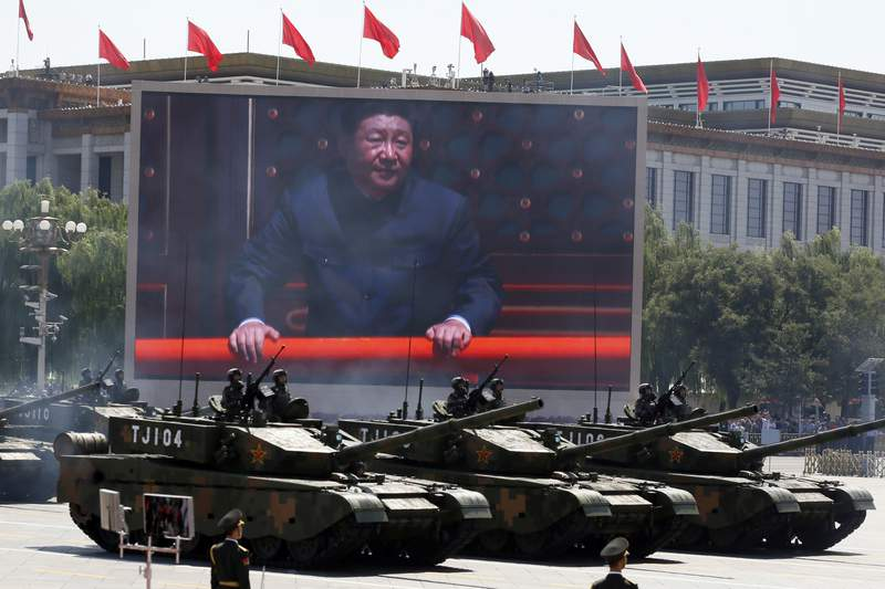 FILE - In this Thursday, Sept. 3, 2015 file photo, Chinese President Xi Jinping is displayed on a screen as Type 99A2 Chinese battle tanks take part in a parade commemorating the 70th anniversary of Japan's surrender during World War II held in front of Tiananmen Gate in Beijing. Seventy-five years after Japan's surrender in World War II, and 30 years after its economic bubble popped, the emergence of a 21st century Asian power is shaking up the status quo. As Japan did, China is butting heads with the established Western powers, which increasingly see its growing economic and military prowess as a threat. (AP Photo/Ng Han Guan, File)