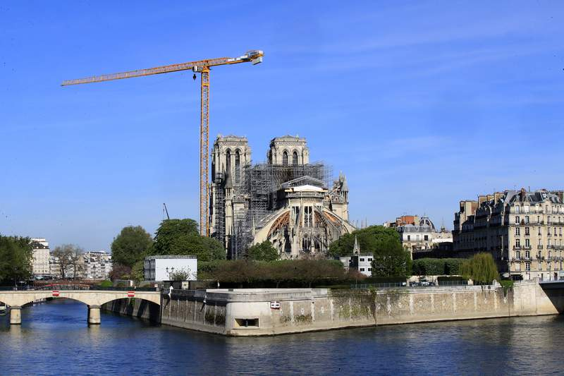 FILE - In this April 15, 2020 file photo, a crane stands by Notre Dame Cathedral Wednesday, April 15, 2020 in Paris. Work began Monday to refit the construction site at fire-damaged Notre Dame Cathedral to protect workers from the virus and allow cleanup efforts to resume. Work on the cathedral halted in mid-March, when France imposed strict confinement measures across the country as virus cases mushroomed. (AP Photo/Michel Euler, File)