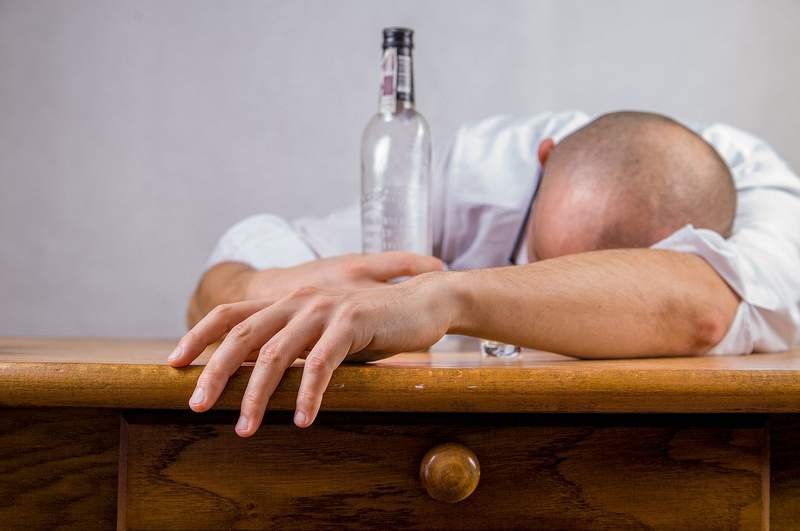 A man lays his head on a table while holding a bottle in his hand.