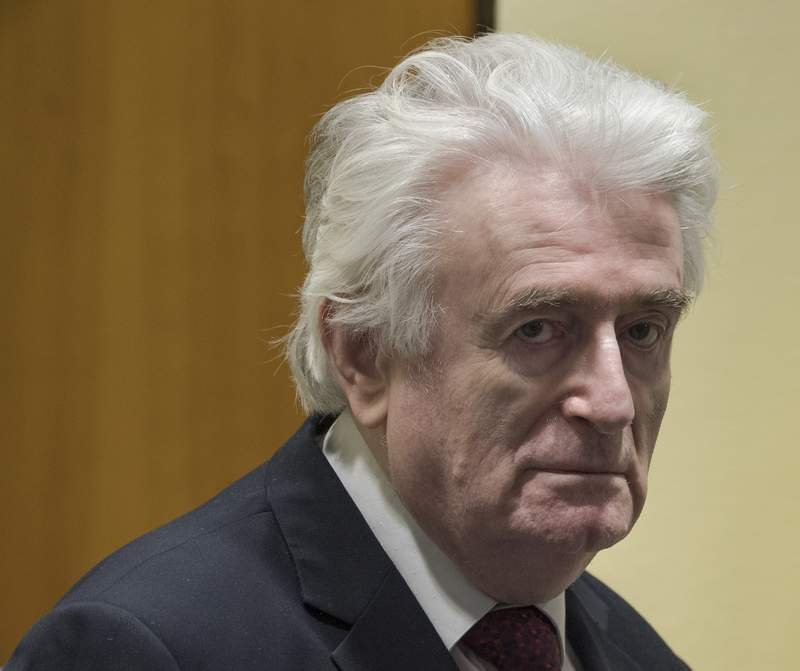 FILE - In this Wednesday, March 20, 2019 file photo, former Bosnian Serb leader Radovan Karadzic enters the court room of the International Residual Mechanism for Criminal Tribunals in The Hague, Netherlands. The British government said Wednesday, May 12, 2021 that former Bosnian Serb leader Radovan Karadzic will serve his life sentence for war crimes in a U.K. prison. Karadzic, one of the chief architects of the slaughter and devastation of Bosnias 1992-95 war, was convicted in 2016 by a United Nations court of genocide, crimes against humanity and war crimes. (AP Photo/Peter Dejong, file)