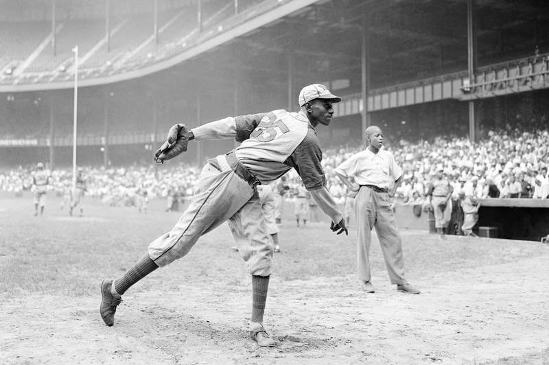 """FILE - In this Aug. 2, 1942, file photo, Kansas City Monarchs pitcher Leroy Satchel Paige warms up at New York's Yankee Stadium before a Negro League game between the Monarchs and the New York Cuban Stars. Major League Baseball has reclassified the Negro Leagues as a major league and will count the statistics and records of its 3,400 players as part of its history. The league said Wednesday, Dec. 16, 2020, it was """"correcting a longtime oversight in the game's history"""" by elevating the Negro Leagues on the centennial of its founding. (AP Photo/Matty Zimmerman, File)"""