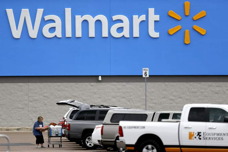 FILE - In this March 31, 2020 file photo, a woman pulls groceries from a cart to her vehicle outside of a Walmart store in Pearl, Miss.  Walmart became a lifeline to millions of people as the coronavirus spread, and its profit and sales surged during the first quarter, topping almost all expectations.  (AP Photo/Julio Cortez, File)