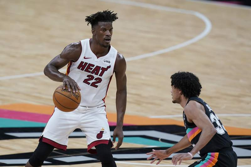 Miami Heat forward Jimmy Butler (22) drives around San Antonio Spurs guard Tre Jones (33) during the second half of an NBA basketball game in San Antonio, Wednesday, April 21, 2021. (AP Photo/Eric Gay)