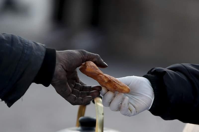 Una mujer que trabaja para una organizacin social entrega un tentempi a un hombre sin hogar en la Avenida 9 de Julio de Buenos Aires, Argentina, el 31 de mayo de 2021. Argentina est luchando contra el aumento de los contagios de COVID-19 con una serie confinamientos intermitentes con grandes consecuencias sobre la pobreza. (AP Foto/Natacha Pisarenko)