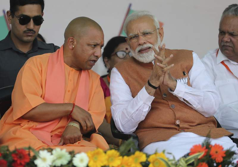 FILE- In this March 28, 2019, file photo, Indian Prime Minister Narendra Modi, right, speaks with Chief Minister of Uttar Pradesh state Yogi Adityanath during an election campaign rally in Meerut, India. Indias ruling Hindu nationalist party has approved legislation in Uttar Pradesh, the countrys most populous state, that lays out a prison term of up to 10 years for anyone found guilty of using marriage to force someone to change religion. The decree was passed Tuesday and follows a campaign by Modis Hindu-nationalist Bharatiya Janata Party against interfaith marriages. The party describes such marriages as love jihad, an unproven conspiracy theory used by its leaders and Hindu hard-line groups to accuse Muslim men of converting Hindu women by marriage. (AP Photo/Altaf Qadri, File)