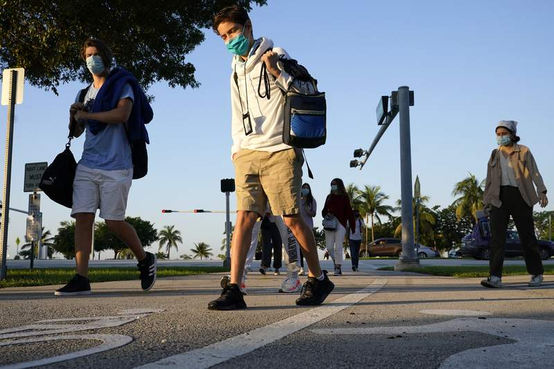 Students arrive for classes at MAST Academy on Tuesday. The Miami maritime and science technology magnet high school was closed Monday after two students reported having COVID-19.