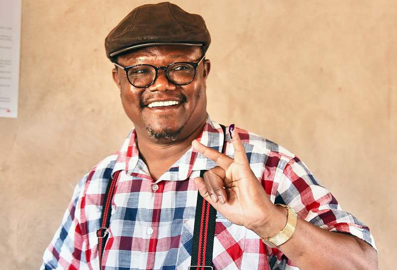 """FILE - In this Wednesday Oct. 28, 2020 file photo, Chadema Presidential Candidate Tundu Lissu smiles as he shows his finger marked with ink after casting his vote at Ntewa Primary School polling station in Ikungi town Singida region, Tanzania. Tanzanian opposition leaders said Monday Nov. 2, 2020, that police have arrested key colleagues and charged them with terrorism-related offenses and sealed off areas where a peaceful protest was to begin over last weeks election that they call too flawed to stand. CHADEMA's presidential candidate, Tundu Lissu, and ACT Wazalendo leader Zitto Kabwe added: """"We believe that there have been attempts to arrest the two of us."""" (AP Photo/File)"""