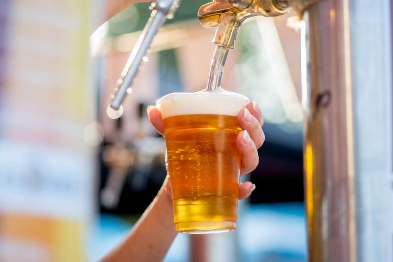 Beer is poured into a glass from a tap.