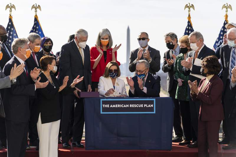 House Speaker Nancy Pelosi of Calif., and Senate Majority Leader Chuck Schumer of N.Y., celebrate after signing the $1.9 trillion COVID-19 relief bill, during an enrollment ceremony on Capitol Hill, Wednesday, March 10, 2021, in Washington. (AP Photo/Alex Brandon)