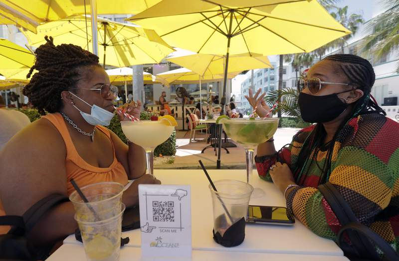 Anita Anderson, left, of Grand Rapids, Mich., and her niece Tawnya Heggins of Houston, chat as they dine outside a restaurant on Miami Beach back on June 26. Miami-Dade's restaurants will be reopening for indoor dining.