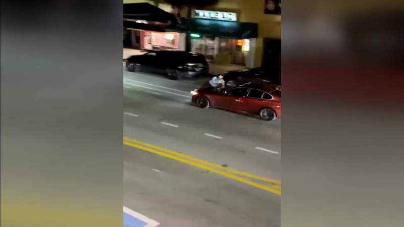 BMW owner jumps on hood of car as woman steals vehicle