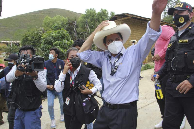 In this photo released by Peruvian news agency Andina, Peru Libre party presidential candidate Pedro Castillo waves at supporters after casting his ballot in the general elections in Cajamarca, Peru, Sunday, April 11, 2021. (POOL via AP)