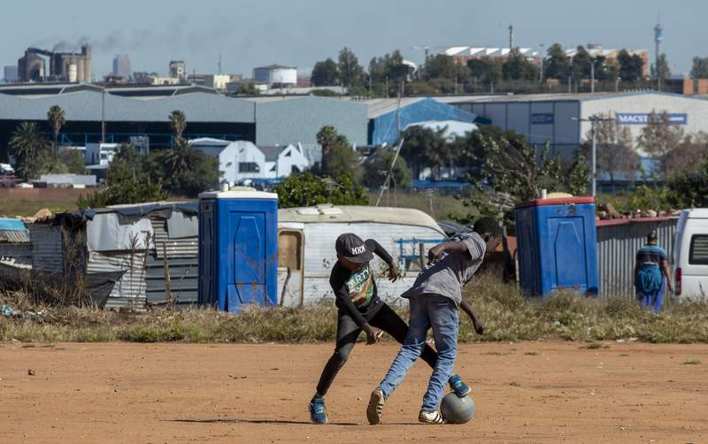 Young boys play soccer on a dusty field at Ramaphosa informal settlement, east of Johannesburg, South Africa, Tuesday, April 28, 2020. South Africa will begin a phased easing of its strict lockdown measures on May 1, although confirmed cases of coronavirus continue to increase. (AP Photo/Themba Hadebe)