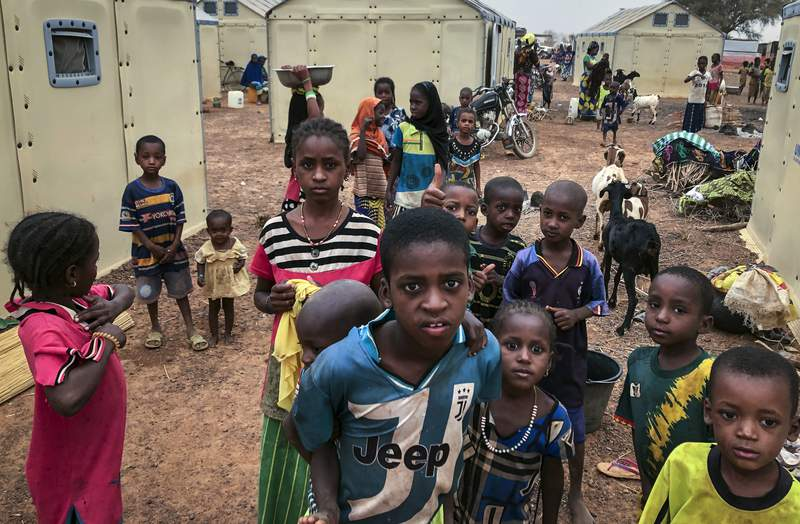 Children of around 6,000 ethnic Fulanis who have been displaced by attacks, gather in a makeshift camp for the displaced in Youba in Yatenga province in Burkina Faso, Monday, April 20, 2020. The West African nation continues to be wracked by violence linked to Islamic extremists and local defense militias, while security forces reportedly killed 31 unarmed men in the country's north earlier this month, hours after the men were detained during a government counterterrorism operation in the town of Djibo in the Sahel region, according to a report released Monday by Human Rights Watch. (AP Photo/Sam Mednick)