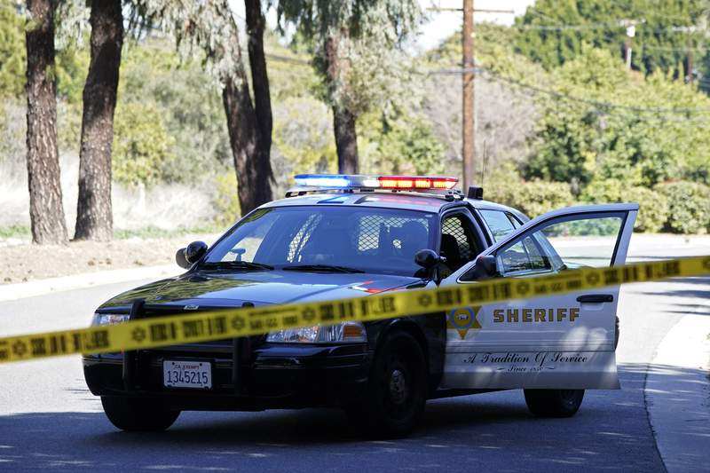 FILE - In this Feb. 23, 2021, file photo, a police car blocks a road in a suburb of Los Angeles. The Associated Press says it will no longer publish the names or photographs of people charged with minor crimes, in a recognition of how such stories can have a long, damaging afterlife on the Internet. (AP Photo/Ashley Landis, File)