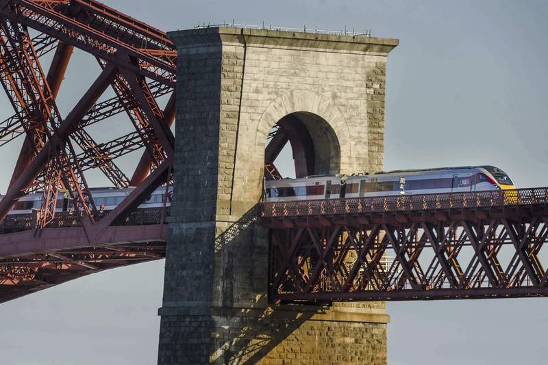 FILE - In this May 6, 2021 file photo, a LNER Azuma train crossing the Forth Bridge in Edinburgh. Britain plans to bring the national rail network back under government control, reversing one of the most controversial elements of the privatization drive carried out by the Conservative governments of the 1980s and 90s. Under plans announced Thursday, May 20, 2021, the government will create a new entity known as Great British Railways that will own all railroad infrastructure, set most fares and schedules, collect ticket revenue and run a single ticketing website. Private companies will continue to operate trains under contracts with the state. (Euan Cherry/PA via AP, File)