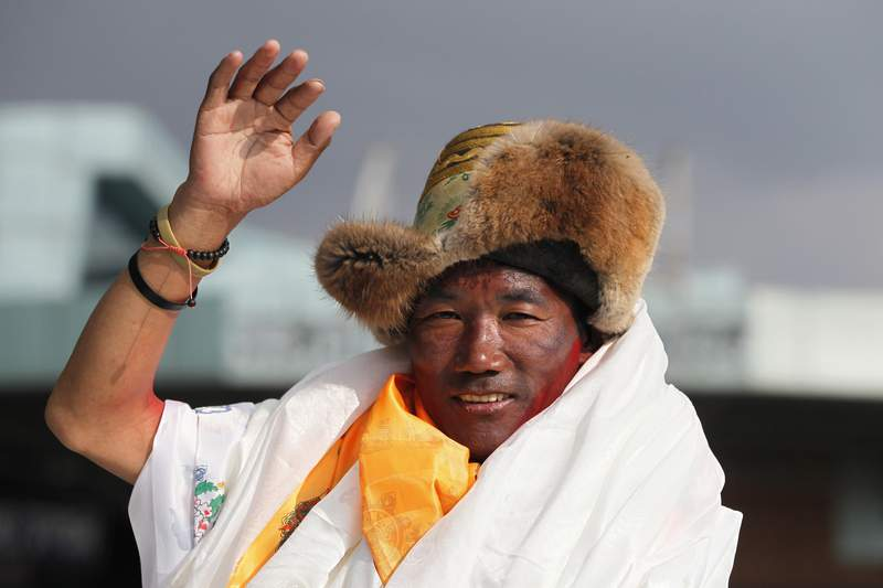 FILE - In this May 20, 2018, file photo, Nepalese veteran Sherpa guide, Kami Rita waves as he arrives in Kathmandu, Nepal. Rita, 51, an ace Sherpa guide scaled Mount Everest Friday for the 25th time breaking his own record for the most successful ascents of the worlds highest peak.  (AP Photo/Niranjan Shrestha, File)