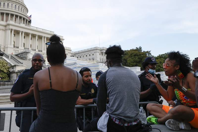 U.S. Capitol police officers talk with demonstrators as they have a conversation about racism in America as they protest the death of George Floyd, Wednesday, June 3, 2020, on Capitol Hill in Washington. Floyd died after being restrained by Minneapolis police officers. At right is Lydia Robinson, 31, of Raleigh, N.C. (AP Photo/Jacquelyn Martin)