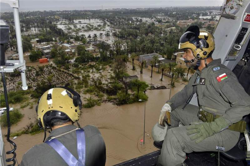 In this photo released by the Oman News Agency, Oman Air Force personnel fly over the Al Khaburah district to assess damage from Cyclone Shaheen, in Oman, Monday, Oct. 4, 2021. The death toll from Cyclone Shaheen rose to five Monday with other fishermen from Iran reported missing as the storm moved further inland into Oman and weakened. (Oman News Agency via AP)