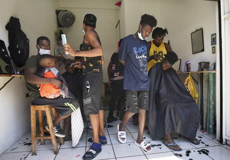 ARCHIVO - En esta foto de archivo del 3 de setiembre de 2021, migrantes haitianos estn en una peluquera improvisada en Tapachula, Mxico. Miles de migrantes, en su mayora haitianos, estn varados en la ciudad surea de Tapachula. Muchos esperan meses, hasta un ao, para que procesen sus pedidos de asilo. (AP Foto/Marco Ugarte, File)