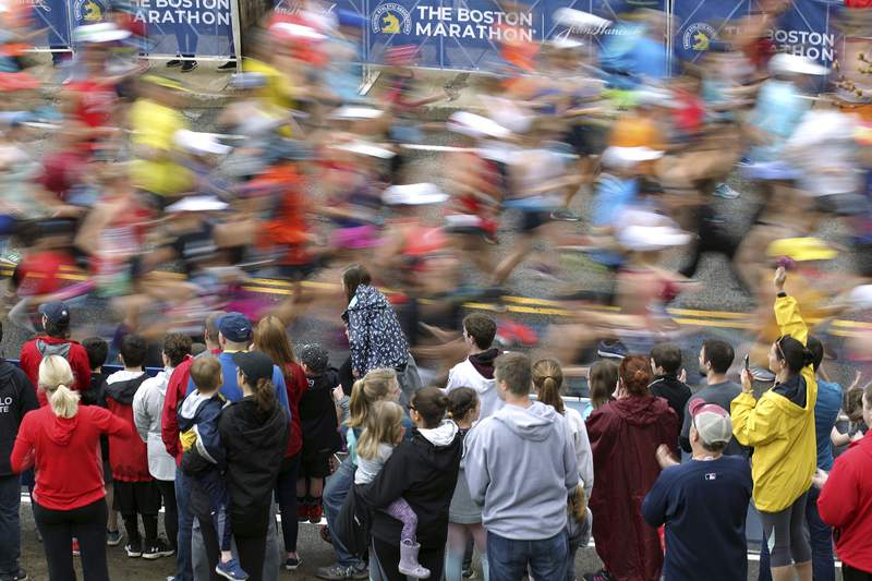FILE - In this April 15, 2019, file photo, fans cheer on the third wave of runners at the start of the 123rd Boston Marathon in Hopkinton, Mass. The 2020 Boston Marathon was canceled because of the COVID-19 pandemic for the first time in its 124-year history. There will be a virtual event instead, where a weeklong TV special beginning Sept. 7, 2020, will showcase runners' stories as they go the distance on their own. (AP Photo/Stew Milne, File)