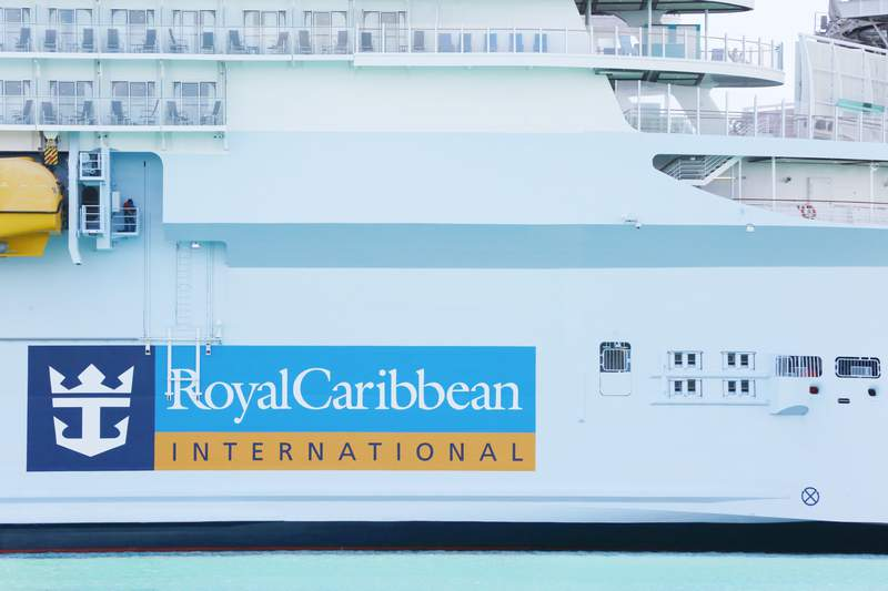 FILE - In this March 14, 2020 file photo, Royal Caribbean International cruise ship docked at PortMiami, among other cruise ships, as the world deals with the coronavirus outbreak in Miami.   Royal Caribbean Group is putting its cruising toes back in the water this summer. The cruise company said Friday, March 19, 2021 that two of its lines  Royal Caribbean and Celebrity Cruises  will resume Caribbean sailings in June.   (AP Photo/Brynn Anderson, File)