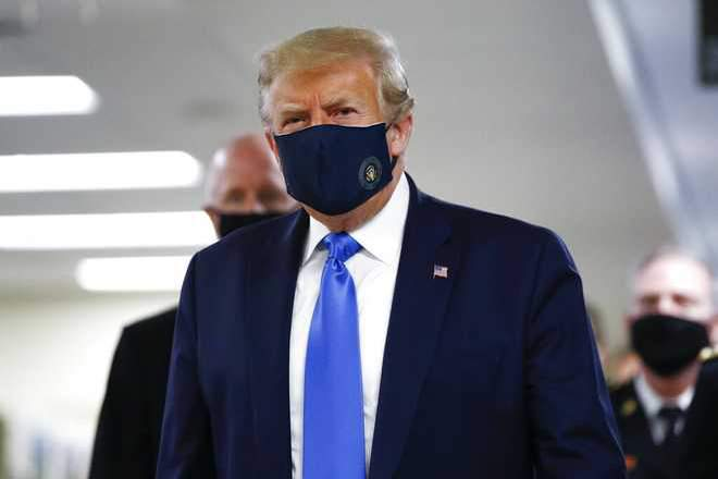 President Donald Trump wears a mask as he walks down the hallway during his visit to Walter Reed National Military Medical Center on Saturday, July 11.