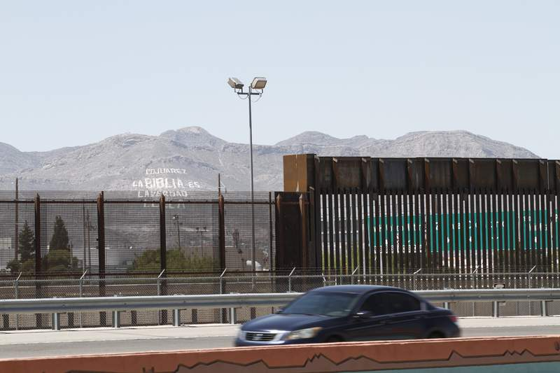 FILE - In this April 22, 2020, photo, a car drives on a highway parallel to a border fence in El Paso, Texas. U.S. Immigration and Customs Enforcement was prepared to release three men convicted of sex offenses against children, Texas prison officials said, in an apparent misapplication by authorities of enforcement directives from President Joe Biden's administration. The three were not released after discussions between the state prison system and immigration authorities. (AP Photo/Cedar Attanasio, File)