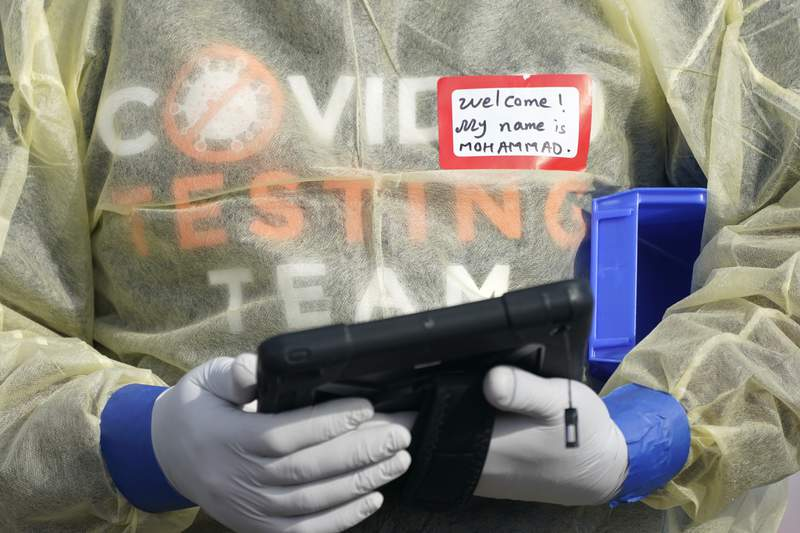 FILE - In this Oct. 28, 2020, file photo, a worker wearing gloves, and other PPE holds a tablet computer as he waits to check people at a King County coronavirus testing site in Auburn, Wash., south of Seattle. The latest surge in U.S. coronavirus cases appears to be larger and more widespread than the two previous ones, and it is all but certain to get worse. But experts say there are also reasons to think the nation is better able to deal with the virus than before, with the availability of better treatments, wider testing and perhaps greater political will. (AP Photo/Ted S. Warren, File)