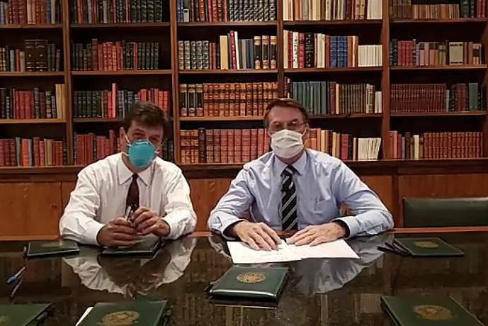In this handout photo released by Brazil's Presidential Press Office, Brazilian Health Minister Luiz Henrique Mandetta, left, and President Jair Bolsonaro, wear masks as they speak about the new coronavirus during a Facebook Live transmission, in Brasilia, Brazil, Thursday, March 12, 2020. Bolsonaro has tested negative for the new coronavirus, according to a post Friday on his official Facebook profile. Bolsonaro, 64, received the test on Thursday after his communications director was confirmed to have the virus.(Brazil's Presidential Press Office via AP)