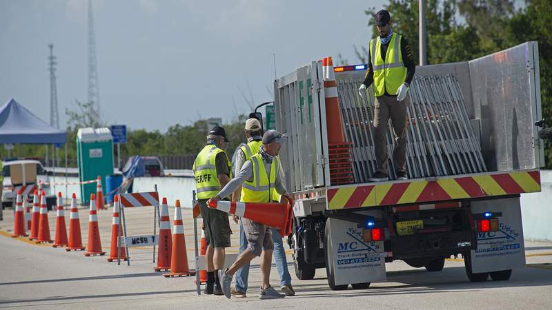 A Monroe County Public Works employee loads traffic cones onto a truck as a checkpoint at the top of the Florida Keys Overseas Highway is dismantled Sunday, May 31, 2020, near Key Largo, Fla. The checkpoint was established March 27, 2020, to close the Keys to visitors in an effort to curb the spread of COVID-19. The Florida Keys are to officially reopen to visitors Monday, June 1. (Andy Newman/Florida Keys News Bureau/HO)