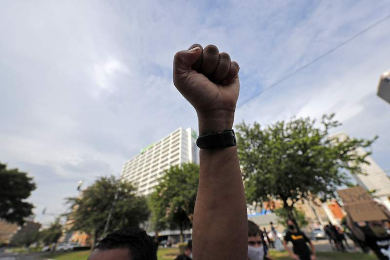 A demonstrator raises a fist in the air during a peaceful march in downtown New Orleans, Tuesday, June 2, 2020. They were protesting over the death of George Floyd, a black man who was in police custody in Minneapolis. Floyd died after being restrained by Minneapolis police officers on Memorial Day.(AP Photo/Gerald Herbert)