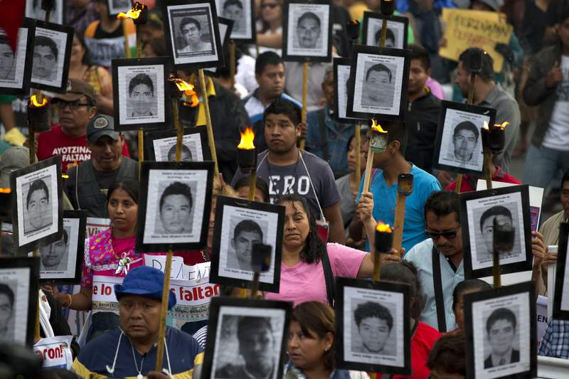 FILE - In this April 26, 2016 file photo, family members and supporters of 43 missing teachers college students carry pictures of the students as they march to demand the case not be closed and that experts' recommendations about new leads be followed, in Mexico City. Nearly six years after 43 students disappeared in Mexicos southern Guerrero state, Attorney General Alejandro Gertz Manero said Tuesday, June 30, 2020 that prosecutors had requested 46 arrest warrants for various municipal level public servants in the state in relation to the case. (AP Photo/Rebecca Blackwell, File)