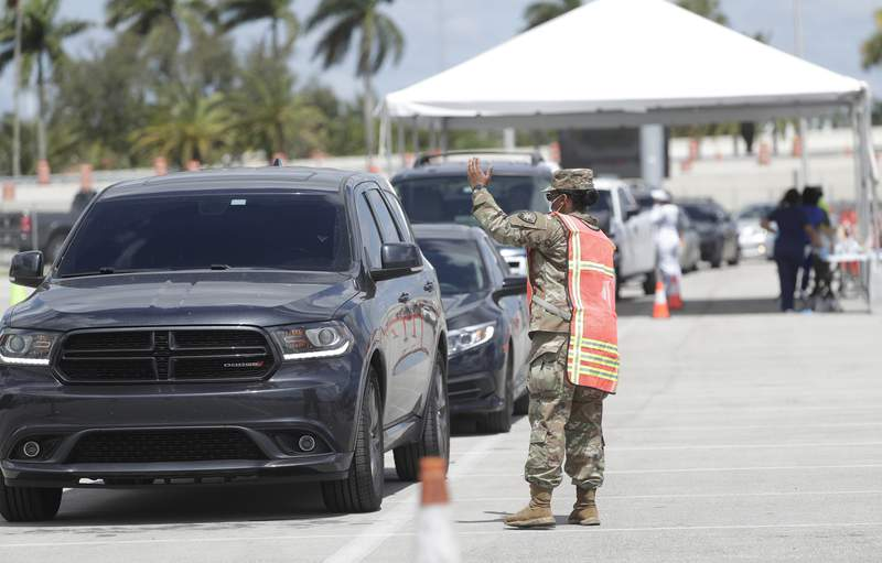 A Florida National Guardsman directs traffic, Sunday, March 22, 2020, at Hard Rock Stadium in Miami Gardens, Fla. The National Guard opened a coronavirus drive-thru testing site Sunday testing first responders. On Monday, they planned to expand it to people at least 65 years old who are showing symptoms of the illness. (AP Photo/Wilfredo Lee)